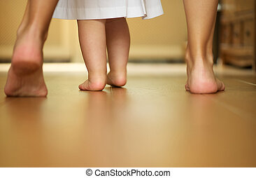 Portrait of a mother teaching baby to walk indoors - Closeup...