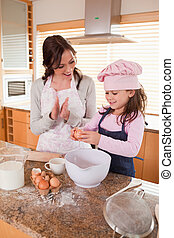 Portrait of a mother teaching her daughter how to bake
