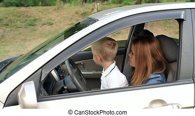 Portrait of a mother with a curious son driving a car, the child learns to drive