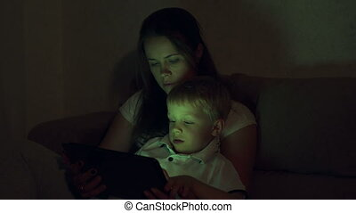 Portrait of a mother with her son with a tablet at home in the dark.