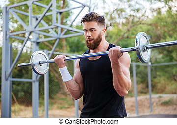 Portrait of a muscular man workout with barbell
