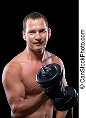 portrait of a naked man with dumbbells on black background