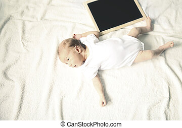 newborn baby and a birthday card on a light background.