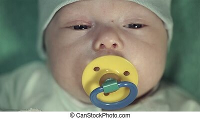 Portrait of a newborn baby boy in the gentle green suit with a yellow pacifier.