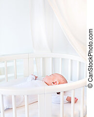 Portrait of a newborn baby boy sleeping in a white round crib wi