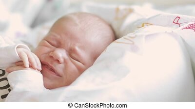 Portrait of a newborn baby crying in sleep with closed eyes, face closeup.