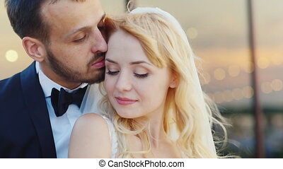 Portrait of a newlywed couple, smiling, wind blowing in her...