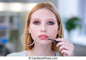 Portrait of a nice attractive woman applying pink lipstick