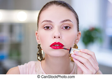 Portrait of a nice attractive woman putting on lipstick - ...