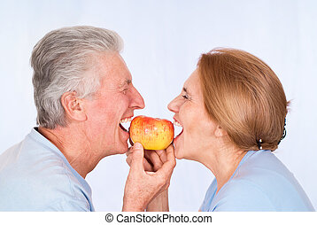 old couple with apple - portrait of a nice old couple with ...