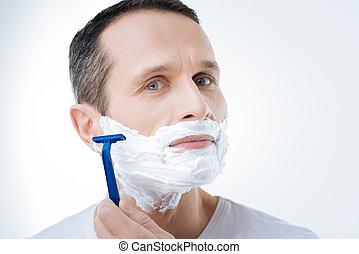 Portrait of a nice pleasant man shaving