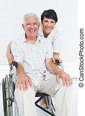 Portrait of a nurse with senior patient sitting in wheelchair