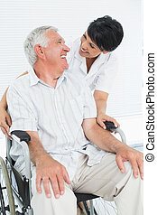 Portrait of a nurse with senior patient sitting in...