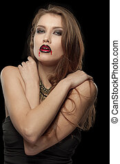 Portrait of a pale gothic vampire woman on a black...