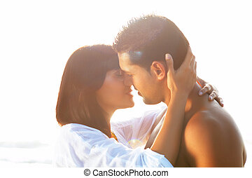 portrait of a passionate couple in love kissing and embracing between backlit