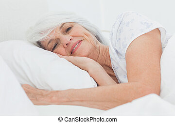 Portrait of a peaceful woman in bed