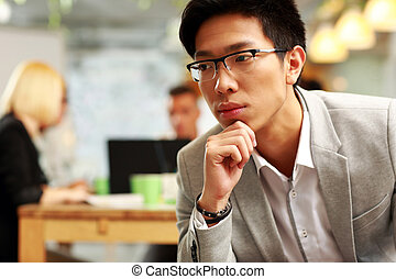 Portrait of a pensive asian man sitting in office, with his colleagues in background