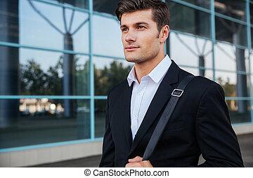 Portrait of a pensive businessman standing outdoors near office building
