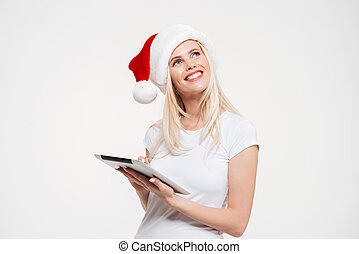 Portrait of a pensive smiling woman in christmas hat holding...