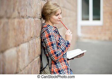 Portrait of a pensive student girl against the brick wall, dreaming