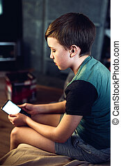 Portrait of a pensive unhappy boy with a smartphone in the room. White screen.