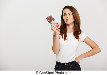 Portrait of a pensive young woman looking at chocolate bar