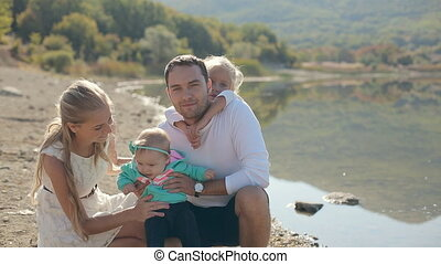 Portrait of a perfect family consisting of mom, dad and two beautiful daughters near the shore