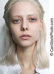 Portrait of a platinum blonde with bright blue eyes looking at the camera.