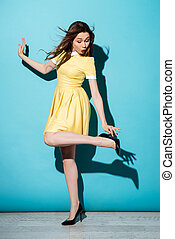 Portrait of a playful pretty woman in dress posing isolated...