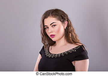 Portrait of a plus size female model posing in black dress over grey background.