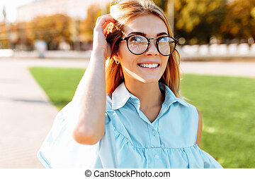 Portrait of a positive beautiful girl with glasses, a student strolling in the Park, in a good mood