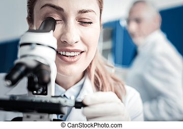 Portrait of a positive female scientist looking into the microscope