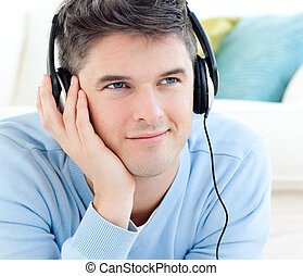 Portrait of a positive man with headphones lying on the floor