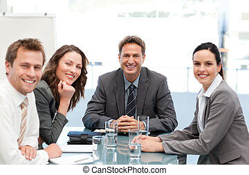 Portrait of a positive team sitting at a table in an office