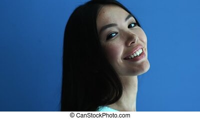 Portrait of a positive woman smiling on blue background