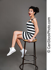 Portrait of a pretty afro american woman sitting on chair