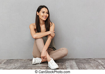 Portrait of a pretty asian woman sitting on a floor