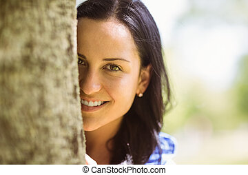 Portrait of a pretty brunette leaning against a tree