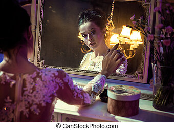 Portrait of a pretty countess touching an antique mirror