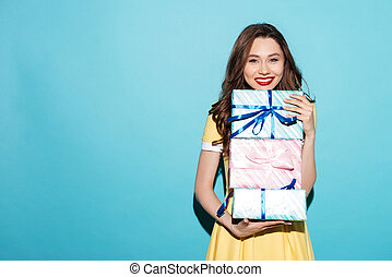 Portrait of a pretty girl holding stack of gift boxes
