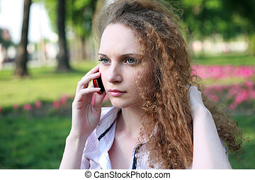 Portrait of a pretty girl with curly phone