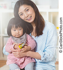 Portrait of a pretty japanese mother holding her cute baby daughter