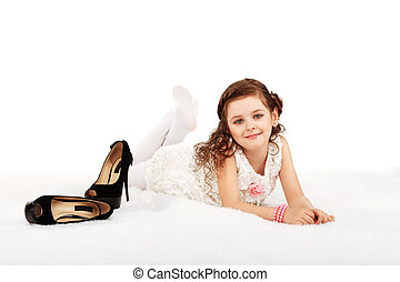Portrait of a pretty little fun fashion girl lying on a fluffy rug on the floor