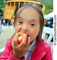 Portrait of a pretty little girl biting a red apple