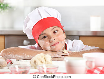 Portrait of a pretty little girl in a cook's suit