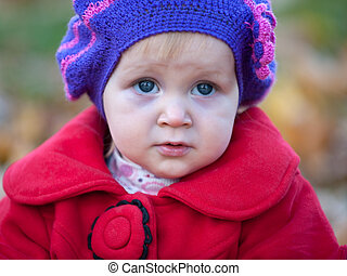Portrait of a pretty little girl in red coat