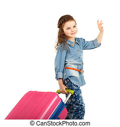 portrait of a pretty little girl with big pink suitcase on wheels