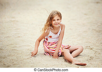 Portrait of a pretty little girl with waving in the wind long hair sitting on the beach