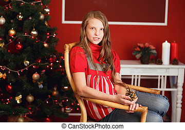 pretty smiling teen girl with long hair in interior with Christmas decorations