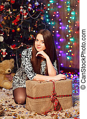 Portrait of a pretty smiling teen girl with long hair in interior with Christmas decorations